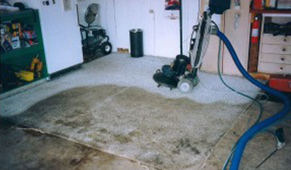 Commercial rug cleaning vacuum on dirty, white rug