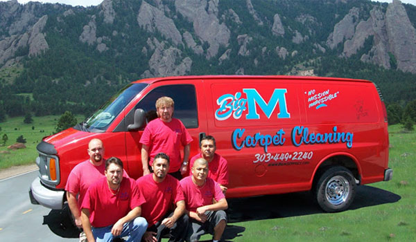Big M Services team standing in front of red work truck